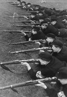 Members of the Hitler Youth learning to shoot rifles.